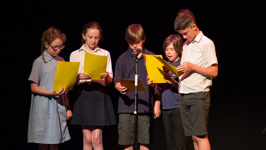 Children stand as agroup, holding pieces of paper and reading into a microphone