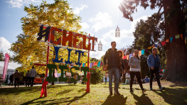 Four people walk past a #CheltLitFest sign, smiling.